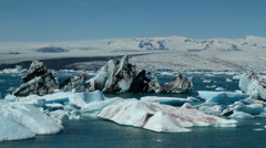 Icebergs melt in the sun  in a vast blue glacier lagoon in the interior of Stock Footage
