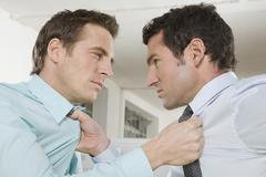 Stock Photo of Germany, Munich, two Business men fighting in office, close-up