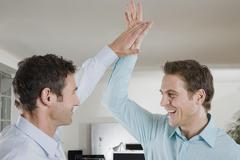 Saksa, München, kaksi liikemiestä toimistossa antaa high five, hymyilee, potretti Kuvituskuvat