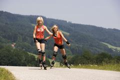 teenage girls (13-15) inline skating - stock photo