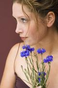 Stock Photo of Young woman holding cornflowers, portrait, close up