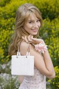 Blond woman with handbag smiling merrily Stock Photos