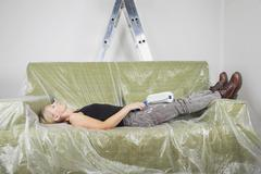 Germany, Cologne, Mature woman resting on plastic foiled sofa holding paint Stock Photos
