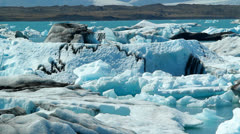 Stock Video Footage of Icebergs float in a vast blue glacier lagoon in the interior of Iceland.