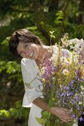 Austria, Salzburger Land, Woman holding bunch of wildflowers, smiling, close up Stock Photos