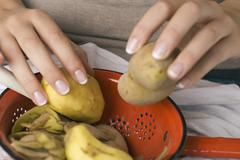 Stock Photo of Person peeling potatoes, close up
