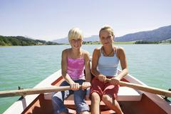 Teenage girls (13-15) rowing boat, smiling, portrait Stock Photos