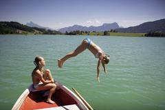 Stock Photo of Teenage girls having fun at a lake, jump into the water!