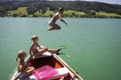 Stock Photo of girls (8-15) sitting on boat, one jumping in water, side view