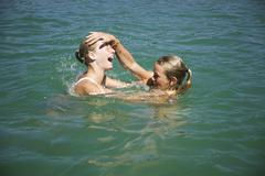 teenage girls (13-15) playing in water, side view - stock photo