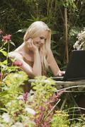 Austria, Woman sitting at table in garden using laptop Stock Photos