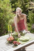 Austria, Woman placing napkin on plates in garden Stock Photos