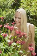 Austria, Woman smelling wildflowers, portrait Stock Photos