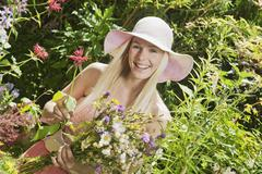 Austria, Woman in garden holding bunch of wildflowers, smiling Stock Photos