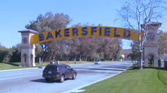 Stock Video Footage of Cars drive into Bakersfield, California under the traditional arched gateway to
