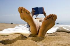 Stock Photo of Woman lying on beach, reading book (focus on foreground)