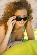 Young woman wearing sun glasses, relaxing on beach Stock Photos