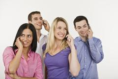 Four persons using mobile phone Stock Photos