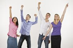 Four persons cheering, hands up Stock Photos