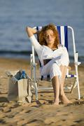 Young woman sitting in deck chair on beach, reading book - stock photo