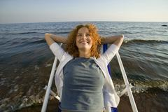 Young woman relaxing in deck chair on beach, smiling, close-up Stock Photos