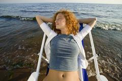 Young woman relaxing in deck chair on beach, looking away, close-up Stock Photos