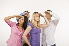 Four persons, hands to head, watching out, portrait Stock Photos
