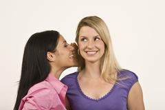 Woman whispering to friend Stock Photos