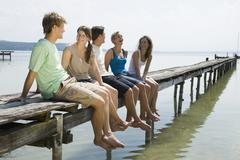 Germany, Bavaria, Ammersee, Young people relaxing on jetty Stock Photos