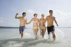 Stock Photo of Germany, Bavaria, Ammersee, Young people running into lake