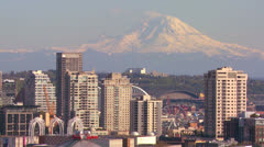 Telephoto shot of Mt. Rainier looming over the skyline of Seattle, Washington. Stock Footage