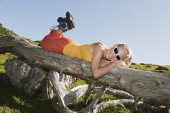 Young woman lying on front on fallen tree trunk, smiling. Stock Photos