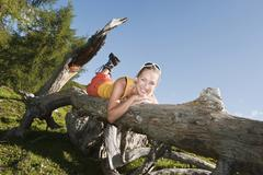 Young woman lying on front on fallen tree trunk, smiling. - stock photo