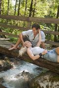 Stock Photo of Austria, Steiermark, Couple resting on wooden bridge over stream