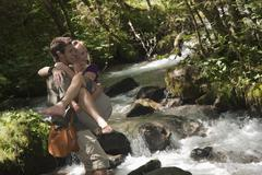 Stock Photo of Austria, Steiermark, Man carrying woman and crossing stream, smiling