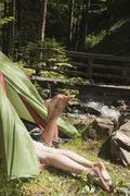 Austria, Steiermark, Young couple lying in tent by stream Stock Photos