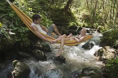 Austria, Steiermark, Young couple lying in hammock above stream - stock photo