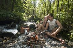 Austria, Steiermark, Young couple sitting at camp fire by stream in forest Stock Photos