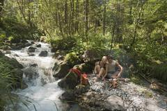 Austria, Steiermark, Young couple sitting at camp fire by stream in forest - stock photo