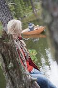 Austria, Obertauern, Woman sitting on tree trunk looking at man in boat - stock photo