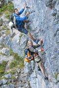 Austria, Steiermark, Ramsau, Silberkarklamm, Young couple climbing rock Stock Photos