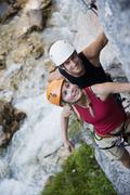 Stock Photo of Austria, Steiermark, Ramsau, Silberkarklamm, Young couple climbing rock, smiling