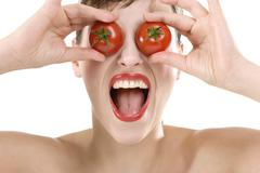 Stock Photo of woman, eyes covered with tomatoes, close-up