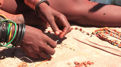 African native tribes - Young Himba girl producing jewelery in Namibia Stock Footage