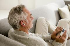 Mature man listening to MP3 player, close-up, elevated view - stock photo