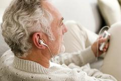 Mature man listening to MP3 player, close-up - stock photo