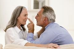 Mature couple sitting, men touching women's nose, close-up Stock Photos