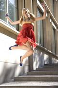 Stock Photo of woman jumping of joy, wearing red dress