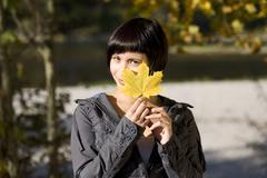 Germany, Bavaria, Portrait of a young woman holding a leaf, smiling Stock Photos