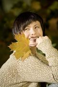 Germany, Bavaria, Young woman holding a leaf, portrait, smiling - stock photo